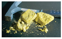 Photograph shows a hammer and a yellow, chalky substance that has been broken in many pieces.