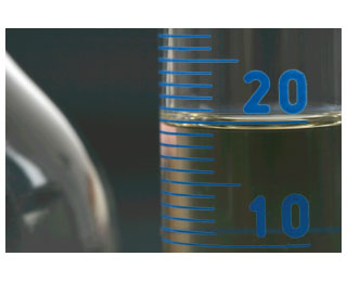 Photograph of liquid in a graduated cylinder with graduations labeled at 10 and 20. The edge of the liquid surface is between the graduations for 20 and 21 and the meniscus is between 19 and 20.