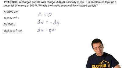 A charged particle with charge +5.0 μC is initially at rest. It is accelerated...