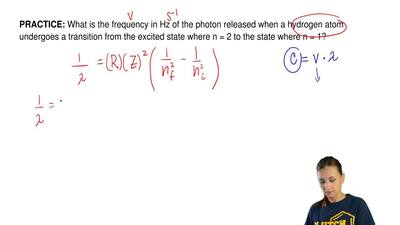 What is the frequency in Hz of the photon released when a hydrogen atom underg...
